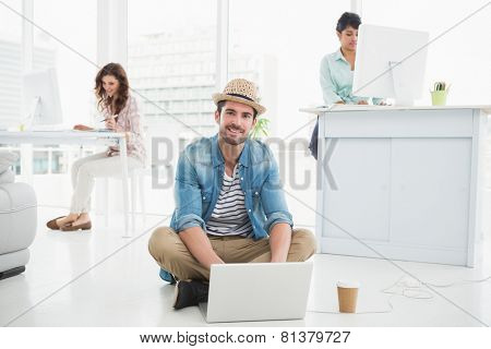 Smiling businessman sitting on the floor using laptop with colleagues behind him