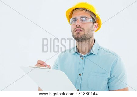 Male supervisor looking away while writing on clipboard on white background