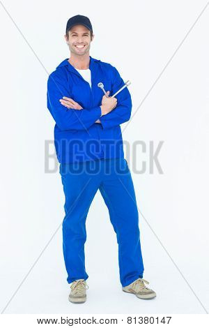 Full length portrait of mechanic holding wheel wrenches over white background