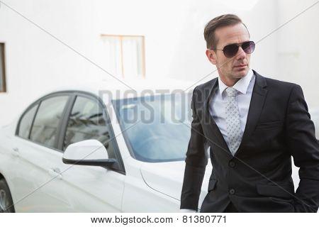 Serious businessman leaning against his car in a car park