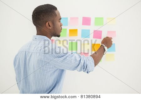 Concentrated businessman reading sticky notes in the office