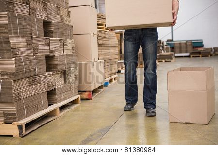Low section of worker carrying box in the warehouse
