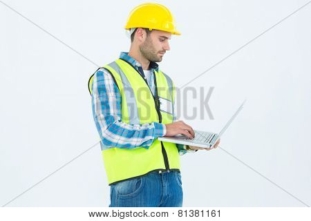 Repairman in reflective workwear using laptop against white background