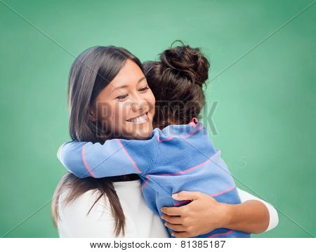 family, children, education, school and happy people concept - happy mother or teacher and little girl hugging over green chalk board background