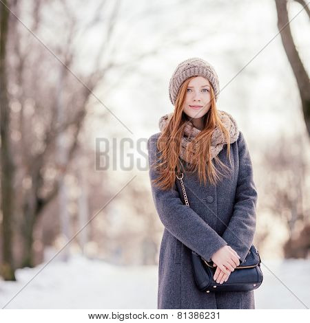 Winter portrait of a cute redhead lady in grey coat and scarf walking in the park