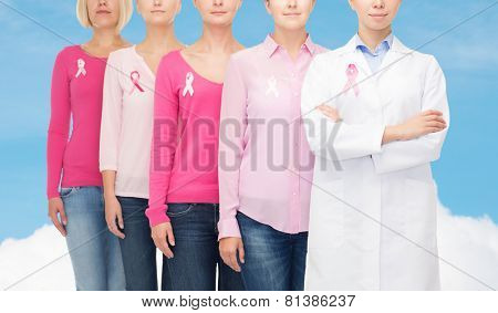 healthcare, people and medicine concept - close up of women in blank shirts with pink breast cancer awareness ribbons over blue sky and white cloud background