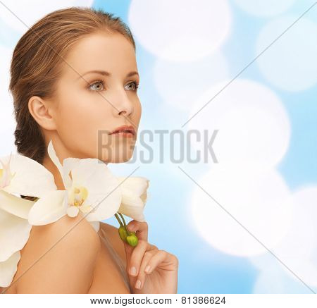 beauty, people and health concept - beautiful young woman with orchid flowers and bare shoulders over blue lights background