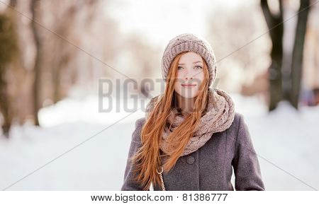 Winter closeup portrait of a cute redhead lady in the park