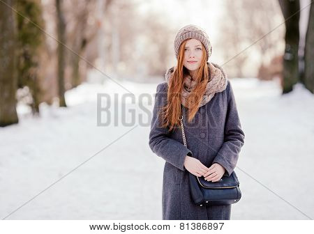 Winter portrait of a cute redhead lady in grey coat and scarf