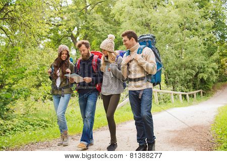 adventure, travel, tourism, hike and people concept - group of smiling friends walking with backpacks and map walking outdoors