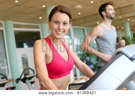 Woman in fitness club using cardio equipment