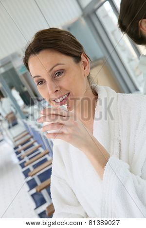 Woman in bathrobe drinking hot tea in relaxation room