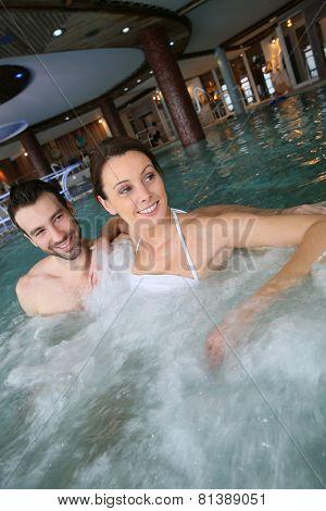 Couple enjoying bath in spa center jacuzzi