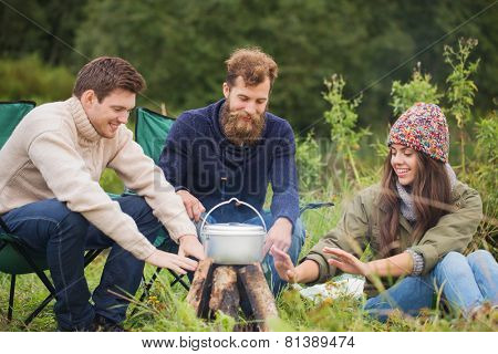adventure, travel, tourism and people concept - group of smiling friends cooking food in dixie and warming hands sitting around bonfire outdoors