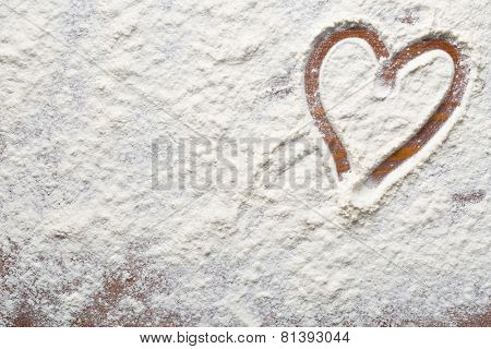 heart of flour on wooden table