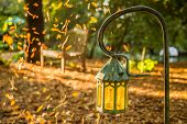 image of lamp shade  - Lamp in the garden with dropped leafs of autumn and blurred background of wooden bench and tree during sunset time - JPG