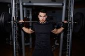 Постер, плакат: Half length portrait of athletic man doing squats working out with barbell