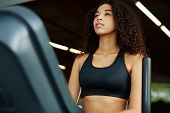 pic of time machine  - Beautiful afro american woman with curly hair exercising in gym on a step simulator machine beautiful and healthy woman enjoying time at gym