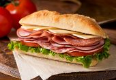 stock photo of deli  - A delicious sandwich with cold cuts lettuce tomato and cheese on fresh ciabatta bread.