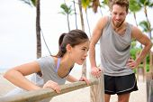stock photo of arm muscle  - Fitness instructor coaching and helping woman doing push - JPG