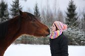 picture of horse girl  - Beautiful teenager girl playfully kissing brown horse in winterforest