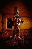 stock photo of chemical weapon  - Two soldiers with the rifles in the gas masks and protective clothes in the old bunker