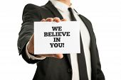 picture of encouraging  - Businessman in a suit holding up a business card with motivational message We believe in you - JPG