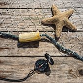 stock photo of starfish  - Nautical border with fishing net sea shells and starfish on a background wooden boards  - JPG