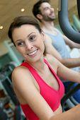 foto of cardio  - Woman in fitness club using cardio equipment - JPG