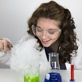 stock photo of tong  - Teenage girl wearing lab coat and doing a science experiment with green and blue liquid with tongs - JPG
