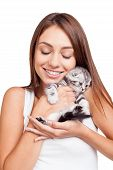pic of bonding  - Beautiful young woman holding little kitten in hands and bonding to him while standing isolated on white background - JPG