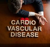 foto of cardio  - Phrase Cardio Vascular Disease made of wooden block letters and devastated middle aged caucasian man in a black suit sitting at the table with the red symbolic heart - JPG