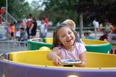 stock photo of amusement park rides  - Four year old girl riding on th etea cups at an amusement park - JPG