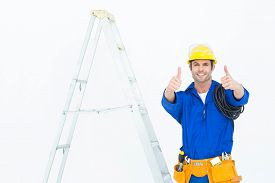picture of step-up  - Portrait of happy electrician gesturing thumbs up while standing by ladder over white background - JPG