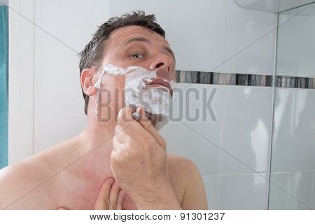 Man Shaving With A Razor Blade And Shaving Cream In Bathroom