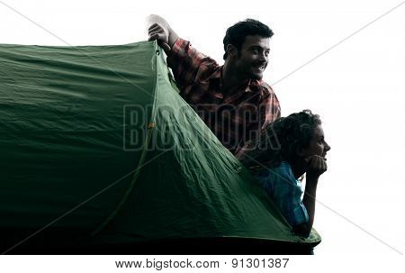 one caucasian couple trekker trekking camping tent nature in silhouette isolated on white background