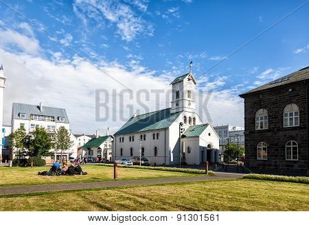 People Relax On The Grass Next To The Church In The Center Of Reykjavik