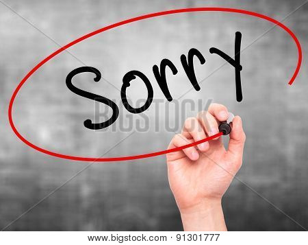 Man Hand writing Sorry with marker on transparent wipe board.
