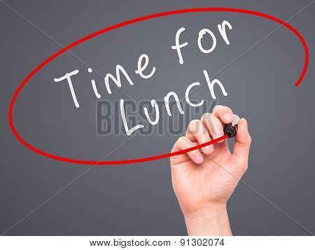Man Hand writing Time for Lunch with marker on transparent wipe board.