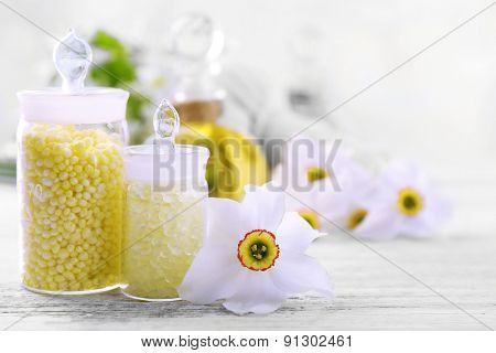 Sea salt, flowers and spa treatment on color wooden table, on light background
