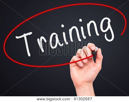 Man Hand writing Training with marker on transparent wipe board.
