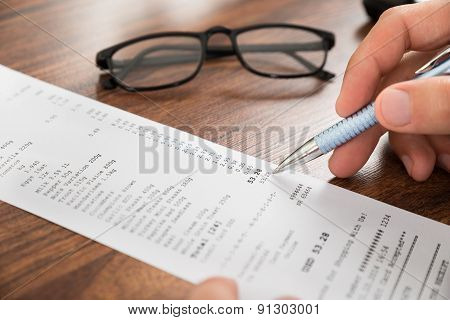 Businessperson Hands With Receipt And Eyeglasses
