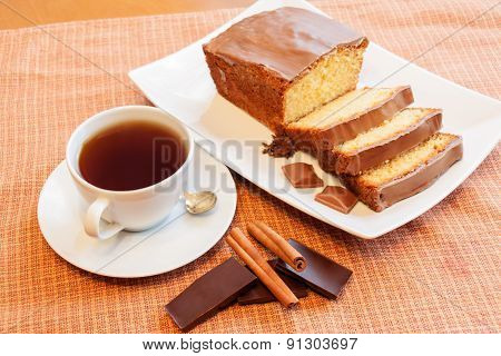 Cup Of Tea And Cake With Glaze Of Chocolate And Spices  In The White Dish