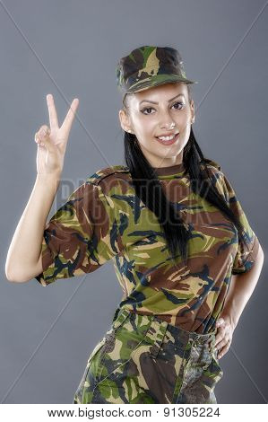 Portrait Of Cheerful Female Soldier Gesturing Peace Sign