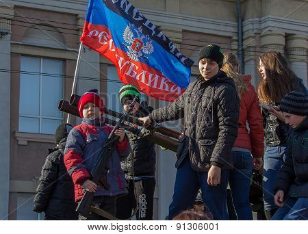 Makeevka, Ukraine - February, 22, 2015: The Boy Is Photographed With A Rifle Under The Flag Of The P