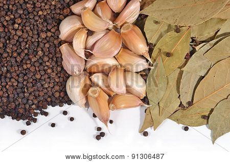Garlic, Bay Leaves And Peppercorns On A White