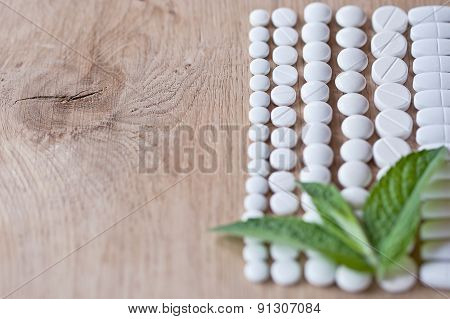 Different White Pills And Foliage Mint