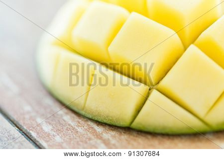 fruits, diet, food and objects concept - close up of ripe mango slice on table