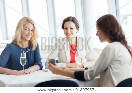 people, holidays, technology and lifestyle concept - happy women with smartphone drinking champagne at restaurant