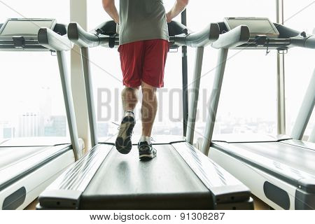 sport, fitness, technology and people concept - close up of male legs running on treadmill in gym